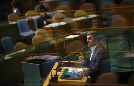 Iran's President Mahmoud Ahmadinejad addresses the United Nations General Assembly as reflections in the glass of a viewing booth show many empty chairs in the chamber after delegates walked out on Ahmadinejad's speech at the U.N. Headquarters in New York, September 22, 2011. REUTERS/Eric Thayer