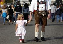 <p>A young festival-goer walks with her father as they visit Oktoberfest in Munich, southern Germany, September 27, 2009. REUTERS/Murad Sezer</p>