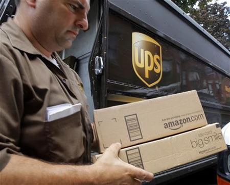 A man delivers two packages from Amazon.com in Boston, Massachusetts in this July 26, 2011 file photo. REUTERS/Brian Snyder