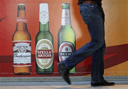 A man walks near the entrance of Anheuser-Busch InBev headquarters in Leuven March 3, 2011. REUTERS/Yves Herman
