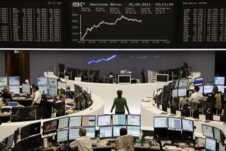 Traders are pictured at their desks in front of the DAX board at the Frankfurt stock exchange, September 26, 2011. REUTERS/Remote/Kirill Iordansky