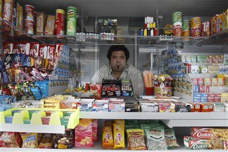 Vendor Dimitris Ptohos poses for a photograph inside his kiosk in Athens, September 25, 2011. REUTERS/John Kolesidis