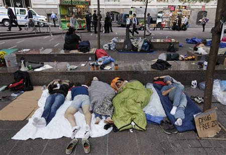 Morning commuters walk past Occupy Wall Street campaign protesters sleeping in Zuccotti Park, near Wall Street in New York September 26, 2011. REUTERS/Brendan McDermid