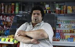 <p>Athens vendor Dimitris Ptohos poses for a photograph in front of his kiosk in Athens September 25, 2011. REUTERS/John Kolesidis</p>