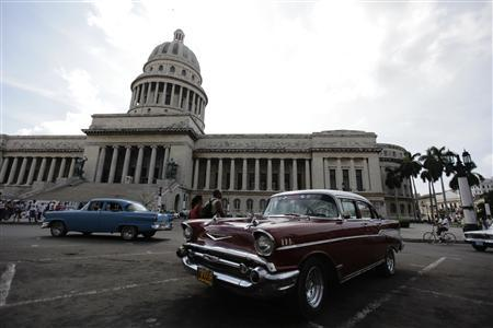 A car is driven past the city capitol building in Havana September 28, 2011. REUTERS/Desmond Boylan