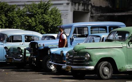 A parking guard stands beside cars parked in Havana September 28, 2011. For the first time since the 1959 revolution, Cubans will have the right to buy and sell cars in a much-anticipated reform under President Raul Control, another step toward greater economic freedom on the communist-led island.REUTERS/Desmond Boylan