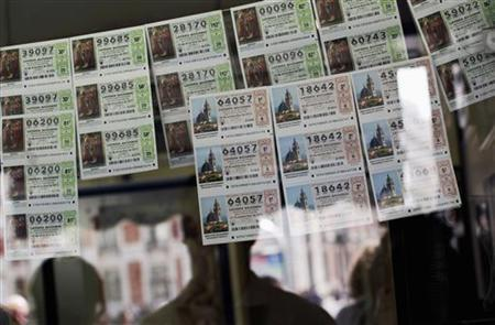 Lottery tickets are displayed behind the window of a lottery stand in Madrid September 23, 2011. REUTERS/Susana Vera