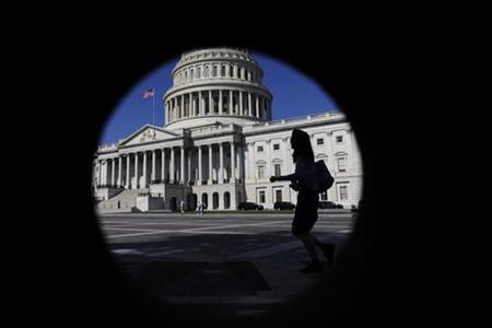 A woman walks past the U.S. Capitol dome, seen through a porthole in nearby brick-work, in Washington, August 2, 2011. REUTERS/Jonathan Ernst