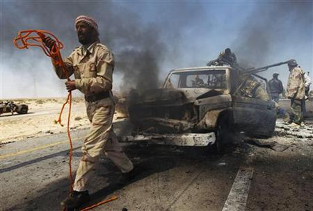A rebel fighter prepares to tow away a government vehicle mounted with heavy machine gun after it was hit by a NATO airstrike on the eastern outskirts of Brega April 5, 2011. REUTERS/Andrew Winning