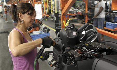 A worker installs parts onto the dashboard for the new Chevrolet Cruze car as it moves along the assembly line at the General Motors Cruze assembly plant in Lordstown, Ohio July 22, 2011. REUTERS/Aaron Josefczyk