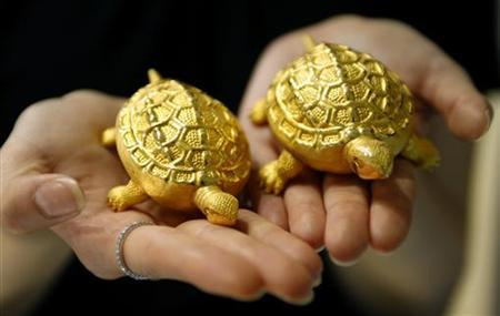 An employee holds replicas of turtles made of gold during a photo opportunity at a jewellery shop in Seoul August 2, 2011. REUTERS/Truth Leem