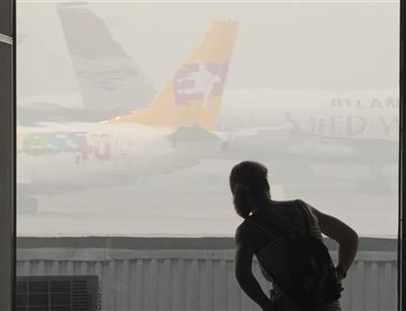 A passenger looks at airplanes shrouded in heavy smog at Vnukovo airport outside Moscow, August 9, 2010. REUTERS/Alexander Natruskin