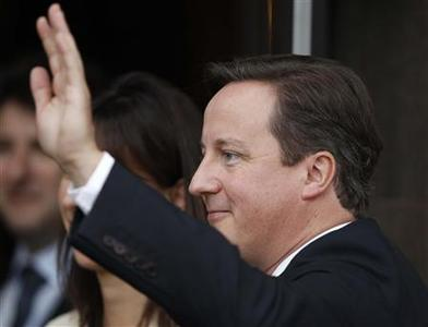 Britain's Prime Minister David Cameron waves as he arrives back at his hotel on the first day of the Conservative Party's annual conference in Manchester, northern England October 2, 2011. REUTERS/Phil Noble