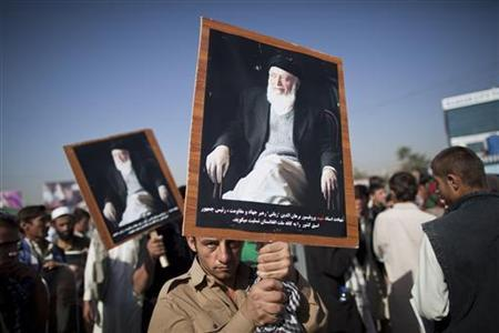 An Afghan man holds a picture of slain former Afghan president and head of the government's peace council, Burhanuddin Rabbani, during a protest in Kabul September 27, 2011. REUTERS/Ahmad Masood