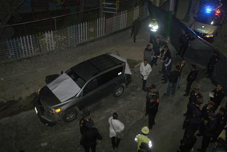 Members of a forensic team and police officers stand at a crime scene where two decapitated body were found inside a car in Mexico City October 3, 2011. REUTERS/Stringer