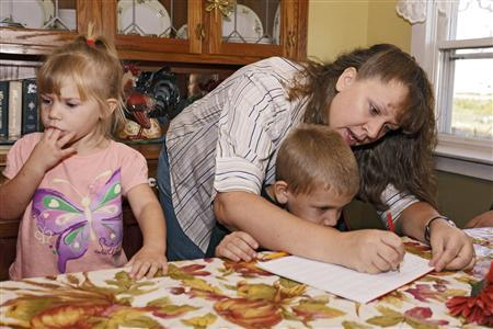 Christa Keagle works with her children Rebekah, 3, and Joshua Keagle, 6, during a homeschool assignment in St. Charles, Iowa September 30, 2011. REUTERS/Brian C. Frank