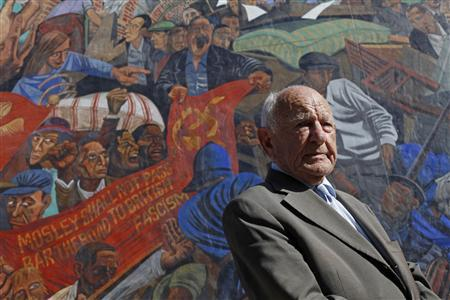 Max Levitas, age 96, poses for a photograph in front of a mural depicting the 1936 battle of Cable Street, on Cable Street, in east London September 28, 2011. Levitas recalls the electricity in the air as more than 100,000 Jews, Irish workers, communists and residents battled police to stop fascists marching through a Jewish area of east London in 1936. REUTERS/Andrew Winning
