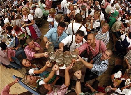 Revellers salute with traditional 1-litre beer mugs at the opening of the Munich Oktoberfest September 17, 2011. REUTERS/Michael Dalder