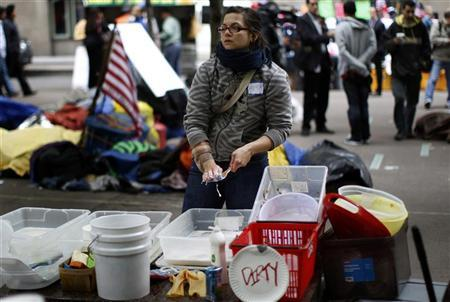 An Occupy Wall Street protester washes dishes at the protesters' camp in Zuccotti Park in lower Manhattan in New York October 3, 2011. REUTERS/Mike Segar