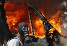 <p>A protester wearing a gas mask walks beside a burning van during violent protests against austerity measures in Athens, June 28, 2011. As strains over Greece mount, rescue efforts have been hampered by cultural differences among the euro zone countries, personality clashes among their leaders, denial in Greece about the extent of the problem and political paralysis that has threatened the economies not just of the euro zone but the rest of the world. Picture taken June 28, 2011. To match Special Report EUROPE/DEJAVU REUTERS/Yannis Behrakis/Files</p>
