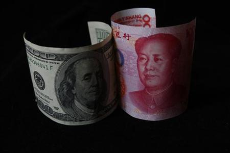 A 100 yuan banknote (R) is placed next to a $100 banknote in this picture illustration taken in Beijing November 7, 2010. REUTERS/Petar Kujundzic