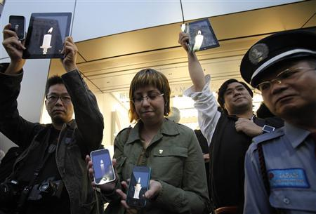 Apple fans take part in a ''candlelight application'' vigil, next to a security guard, outside the Apple store in Tokyo's Ginza district, October 6, 2011. REUTERS/Yuriko Nakao