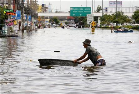 A resident pushes his belongings as he wade through a flooded street in Ayutthaya province, north of Bangkok, October 6, 2011. REUTERS/Chaiwat Subprasom