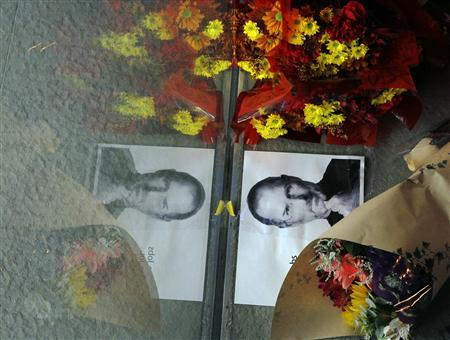 Flowers and a photograph of Steve Jobs are placed against the window outside an Apple store in Boston, Massachusetts October 5, 2011. REUTERS/Brian Snyder