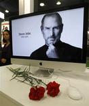 <p>Carnations are placed before a computer screen showing a portrait of Apple co-founder and former CEO Steve Jobs at an Apple store in St. Petersburg October 6, 2011. REUTERS/Alexander Demianchuk</p>