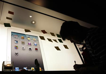 A man writes a note outside the Apple store in Hong Kong October 6, 2011. REUTERS/Tyrone Siu
