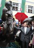 <p>Austrian actor, former champion bodybuilder and former California governor Arnold Schwarzenegger, unveils a statue of himself in a bodybuilding pose as his son Patrick (R) watches, in Thal October 7. 2011. Schwarzenegger officially opened a museum dedicated to his life in the house he was born on Friday. REUTERS/Heinz-Peter Bader</p>