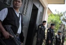 <p>Police officers stand guard while others search a house in Coban, some 200 km (124 miles) northeast Guatemala City, September 9, 2011. REUTERS/Jorge Dan Lopez</p>