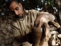 <p>A man works at a small pottery factory in Cairo March 6, 2011. REUTERS/Peter Andrews</p>