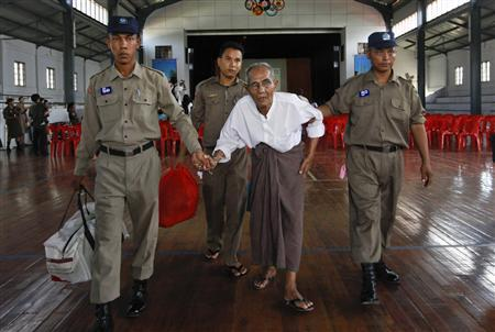 Police assist a newly released prisoner in the meeting hall of Insein Prison in Yangon October 12, 2011. REUTERS/Soe Zeya Tun