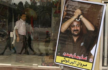 Members of Hamas national security forces are reflected in a souvenir shop window with a poster of jailed Fatah leader Marwan Al-Barghouti as they patrol a street to celebrate a prisoner swap between Hamas and Israel, in Gaza City October 12, 2011. REUTERS/Mohammed Salem