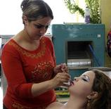 <p>A woman applies lipstick at a beauty parlour in Baghdad September 21, 2011. REUTERS/Stringer</p>