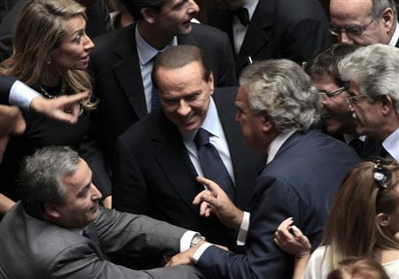 Italian Prime Minister Silvio Berlusconi reacts next to national coordinator of the People of Freedom Denis Verdini (R) in the lower chamber of the deputies in Rome, October 14, 2011. REUTERS/Alessandro Bianchi
