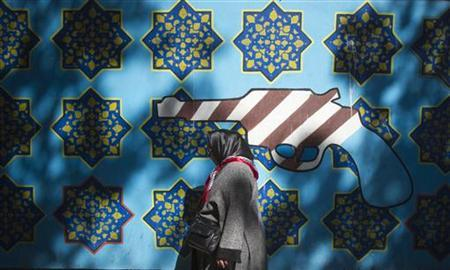 An Iranian woman walks past an anti-U.S. mural on the wall of the former U.S. embassy in Tehran October 12, 2011. REUTERS/Morteza Nikoubazl