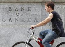 <p>A cyclist passes the Bank of Canada building in Ottawa July 19, 2011. REUTERS/Chris Wattie</p>