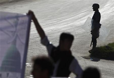 An anti-riot Afghan policeman (R) keeps watch during a protest in Kabul September 27, 2011. REUTERS/Ahmad Masood