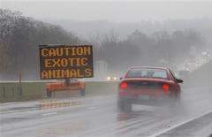 <p>Message mettant en garde les automibilistes sur la présence possible d'animaux dangereux sur une voie rapide près de Zanesville, dans l'Ohio. La police du comté de Muskingum, dans l'est de l'Ohio, a été mobilisée pour participer à un curieux safari afin de neutraliser des dizaines d'animaux dangereux, dont des lions, des tigres, des guépards et des ours, échappés d'une ferme. /Photo prise le 19 octobre 2011/REUTERS/Matt Sullivan</p>