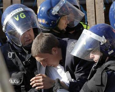 Riot police remove a man at the Dale Farm Traveller site near Billericay, October 19, 2011. REUTERS/Suzanne Plunkett