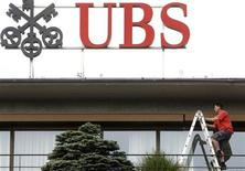 <p>A worker climbs on a ladder under the logo of Swiss bank UBS at the company's headquarters in Zurich May 26, 2011. REUTERS/Arnd Wiegmann</p>