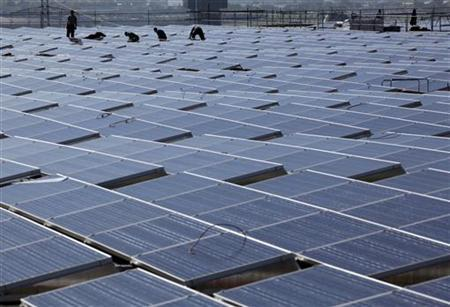 Workers install solar panels on the roof of the Palexpo Exhibition Center in Geneva October 12, 2011. REUTERS/Denis Balibouse