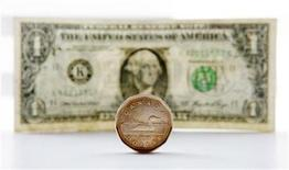 "<p>A Canadian dollar coin, commonly called a ""Loonie"" and an American dollar bill are seen in this staged photo in Toronto, March 17, 2010. REUTERS/Mark Blinch</p>"