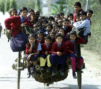 Indian children ride in a cart on the way home from school in the outskirts of New Delhi in this file picture taken, February 26, 2001. The world's population will reach seven billion on 31 October 2011, according to projections by the United Nations, which says this global milestone presents both an opportunity and a challenge for the planet. REUTERS/Pawel Kopcznski/Files