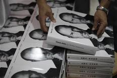<p>Un hombre toma una copia de la biografia autorizada de Steve Jobs en ingles cerca de otras copias en chino en una tienda en Shanghai. Oct 24, 2011. REUTERS/Aly Song</p>