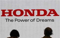 <p>Visitors are silhouetted against a Logo of the Honda Motor at the company showroom in Tokyo October 31, 2011. REUTERS/Issei Kato</p>