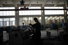 <p>A labourer works at a valve factory in Wenzhou, Zhejiang Province October 18, 2011. REUTERS/Carlos Barria</p>