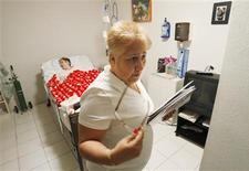 <p>Linda Carmona-Sanchez tends to her critically-ill and bed-ridden daughter Carmen, 28, at their home in Kendall, Florida October 4, 2011. REUTERS/Hans Deryk</p>